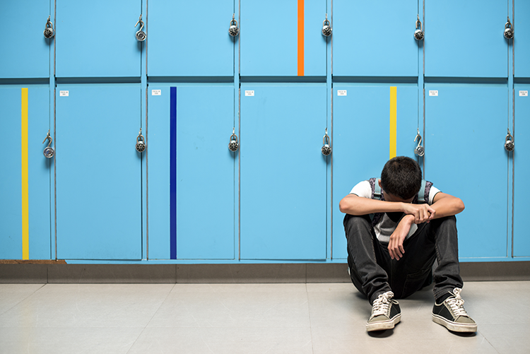 Sad student sits in front of lockers.