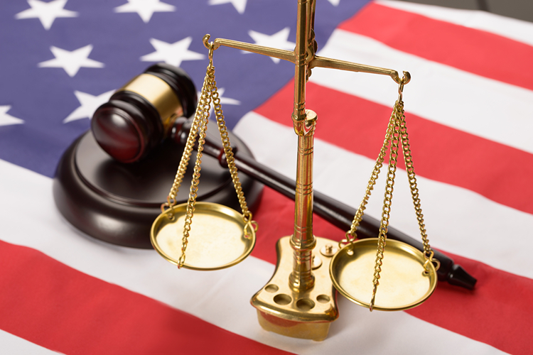 scales of justice and a gavel on an american flag background.