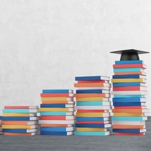 Book stacks and graduation cap.