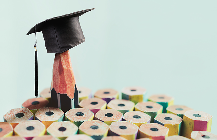 Sharpened pencil rising above unsharpened pencils, wearing a graduation cap.