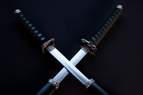 Two Japanese swords with partially drawn blades on dark background