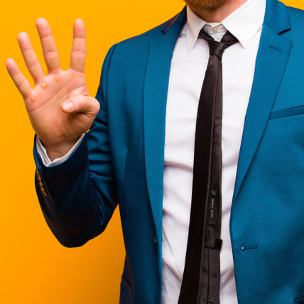 man in suit holding up four fingers
