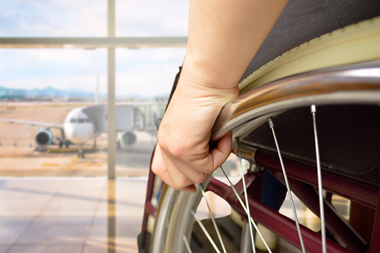 person in a wheelchair looking at an airplane through an airport window