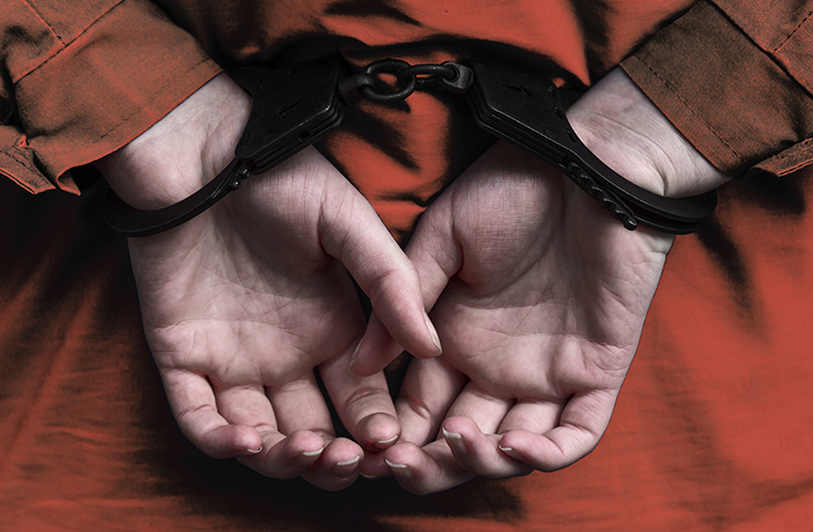 woman in orange prison jumpsuit with hands cuffed behind her back.