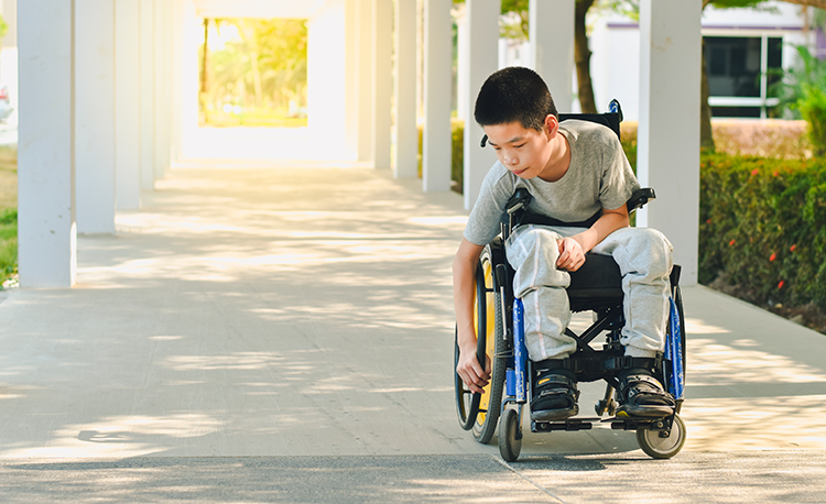 Young boy in a wheelchair sits in a hallway.